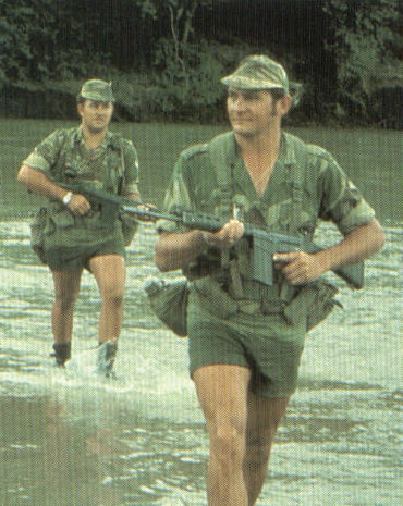 Scouts cross a river deep in the Rhodesian bush.